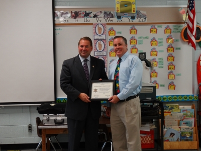 Sheriff Shaun presents a plaque to the Dr. James Quinn, principal of the Newbury Elementary School in Howell Township